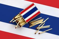 Le drapeau de la Thaïlande est montré sur une boîte d'allumettes ouverte, de laquelle plusieurs matchs tombent et des mensonges s image stock