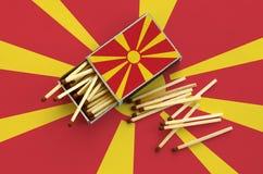 Le drapeau de Macédoine est montré sur une boîte d'allumettes ouverte, de laquelle plusieurs matchs tombent et des mensonges sur  photographie stock libre de droits