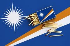 Le drapeau de Marshall Islands est montré sur une boîte d'allumettes ouverte, de laquelle plusieurs matchs tombent et des mensong photos libres de droits