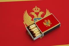 Le drapeau de Monténégro est montré dans une boîte d'allumettes ouverte, qui est remplie de matchs et se trouve sur un grand drap images stock