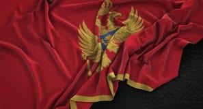 Le drapeau de Monténégro a ridé sur le fond foncé 3D rendent Photo stock