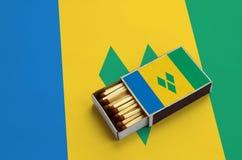 Le drapeau de Saint-Vincent-et-les-Grenadines est montré dans une boîte d'allumettes ouverte, qui est remplie de matchs et se tro photo libre de droits