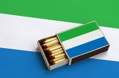 Le drapeau de Sierra Leone est montré dans une boîte d'allumettes ouverte, qui est remplie de matchs et se trouve sur un grand dr photo libre de droits
