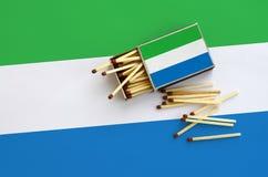 Le drapeau de Sierra Leone est montré sur une boîte d'allumettes ouverte, de laquelle plusieurs matchs tombent et des mensonges s photographie stock