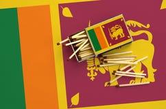 Le drapeau de Sri Lanka est montré sur une boîte d'allumettes ouverte, de laquelle plusieurs matchs tombent et des mensonges sur  photographie stock
