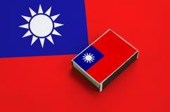Le drapeau de Taïwan est décrit sur une boîte d'allumettes qui se trouve sur un grand drapeau image stock