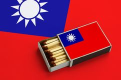 Le drapeau de Taïwan est montré dans une boîte d'allumettes ouverte, qui est remplie de matchs et se trouve sur un grand drapeau images stock