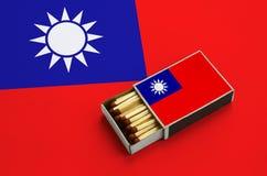 Le drapeau de Taïwan est montré dans une boîte d'allumettes ouverte, qui est remplie de matchs et se trouve sur un grand drapeau photographie stock