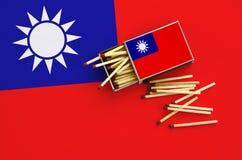 Le drapeau de Taïwan est montré sur une boîte d'allumettes ouverte, de laquelle plusieurs matchs tombent et des mensonges sur un  images libres de droits