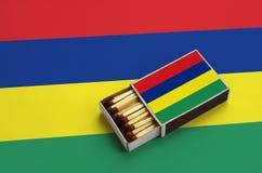 Le drapeau des Îles Maurice est montré dans une boîte d'allumettes ouverte, qui est remplie de matchs et se trouve sur un grand d photos stock
