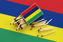 Le drapeau des Îles Maurice est montré sur une boîte d'allumettes ouverte, de laquelle plusieurs matchs tombent et des mensonges  photos libres de droits
