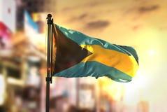 Le drapeau des Bahamas sur le fond brouillé par ville au dos de lever de soleil photos stock
