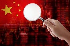 Le drapeau des données d'actions de tendance à la baisse de la Chine diagram avec la main tenant l'agrandissement Images stock