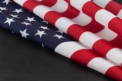 Le drapeau des Etats-Unis se plie sur le tableau avec l'espace de copie Photographie stock