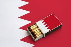 Le drapeau du Bahrain est montré dans une boîte d'allumettes ouverte, qui est remplie de matchs et se trouve sur un grand drapeau photographie stock