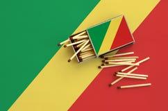 Le drapeau du Congo est montré sur une boîte d'allumettes ouverte, de laquelle plusieurs matchs tombent et des mensonges sur un g photo libre de droits