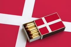 Le drapeau du Danemark est montré dans une boîte d'allumettes ouverte, qui est remplie de matchs et se trouve sur un grand drapea images stock