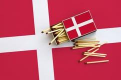Le drapeau du Danemark est montré sur une boîte d'allumettes ouverte, de laquelle plusieurs matchs tombent et des mensonges sur u images stock