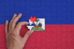 Le drapeau du Haïti est dépeint sur un puzzle, que la main du ` s d'homme accomplit pour plier photos stock