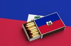 Le drapeau du Haïti est montré dans une boîte d'allumettes ouverte, qui est remplie de matchs et se trouve sur un grand drapeau images stock