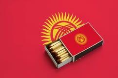 Le drapeau du Kirghizistan est montré dans une boîte d'allumettes ouverte, qui est remplie de matchs et se trouve sur un grand dr photos stock