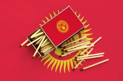 Le drapeau du Kirghizistan est montré sur une boîte d'allumettes ouverte, de laquelle plusieurs matchs tombent et des mensonges s photographie stock