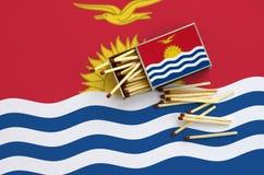 Le drapeau du Kiribati est montré sur une boîte d'allumettes ouverte, de laquelle plusieurs matchs tombent et des mensonges sur u photographie stock libre de droits