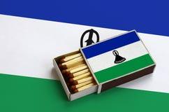 Le drapeau du Lesotho est montré dans une boîte d'allumettes ouverte, qui est remplie de matchs et se trouve sur un grand drapeau photographie stock