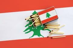 Le drapeau du Liban est montré sur une boîte d'allumettes ouverte, de laquelle plusieurs matchs tombent et des mensonges sur un g images libres de droits