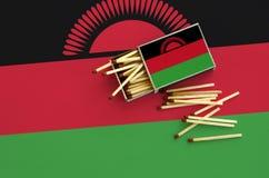 Le drapeau du Malawi est montré sur une boîte d'allumettes ouverte, de laquelle plusieurs matchs tombent et des mensonges sur un  photos stock