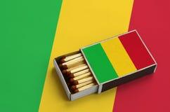 Le drapeau du Mali est montré dans une boîte d'allumettes ouverte, qui est remplie de matchs et se trouve sur un grand drapeau images libres de droits