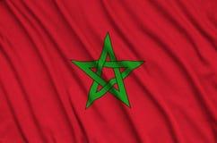 Le drapeau du Maroc est dépeint sur un tissu de tissu de sports avec beaucoup de plis Bannière d'équipe de sport photos stock