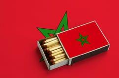 Le drapeau du Maroc est montré dans une boîte d'allumettes ouverte, qui est remplie de matchs et se trouve sur un grand drapeau images stock