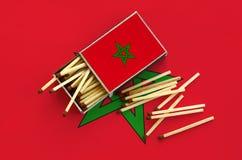 Le drapeau du Maroc est montré sur une boîte d'allumettes ouverte, de laquelle plusieurs matchs tombent et des mensonges sur un g photo stock