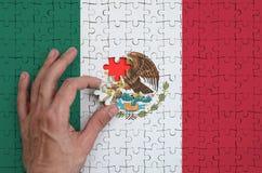 Le drapeau du Mexique est dépeint sur un puzzle, que la main du ` s d'homme accomplit pour plier photos stock