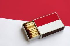 Le drapeau du Monaco est montré dans une boîte d'allumettes ouverte, qui est remplie de matchs et se trouve sur un grand drapeau photographie stock libre de droits