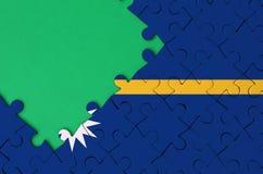 Le drapeau du Nauru est dépeint sur un puzzle denteux réalisé avec l'espace vert gratuit de copie du côté gauche images stock