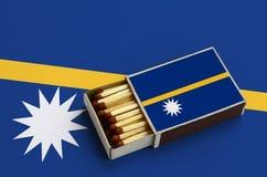 Le drapeau du Nauru est montré dans une boîte d'allumettes ouverte, qui est remplie de matchs et se trouve sur un grand drapeau photos libres de droits