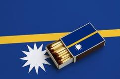 Le drapeau du Nauru est montré dans une boîte d'allumettes ouverte, qui est remplie de matchs et se trouve sur un grand drapeau photos stock