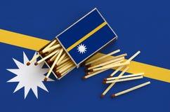 Le drapeau du Nauru est montré sur une boîte d'allumettes ouverte, de laquelle plusieurs matchs tombent et des mensonges sur un g image libre de droits