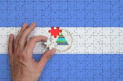 Le drapeau du Nicaragua est dépeint sur un puzzle, que la main du ` s d'homme accomplit pour plier image libre de droits