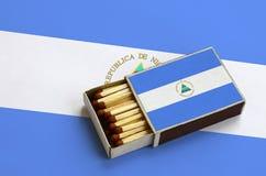 Le drapeau du Nicaragua est montré dans une boîte d'allumettes ouverte, qui est remplie de matchs et se trouve sur un grand drape images stock