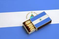 Le drapeau du Nicaragua est montré dans une boîte d'allumettes ouverte, qui est remplie de matchs et se trouve sur un grand drape images libres de droits