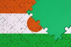 Le drapeau du Niger est dépeint sur un puzzle denteux réalisé avec l'espace vert gratuit de copie du côté droit photos libres de droits
