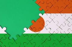 Le drapeau du Niger est dépeint sur un puzzle denteux réalisé avec l'espace vert gratuit de copie du côté gauche illustration libre de droits