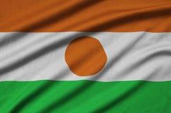 Le drapeau du Niger est dépeint sur un tissu de tissu de sports avec beaucoup de plis Bannière d'équipe de sport photos stock
