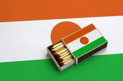 Le drapeau du Niger est montré dans une boîte d'allumettes ouverte, qui est remplie de matchs et se trouve sur un grand drapeau photos stock