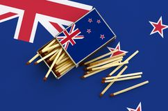 Le drapeau du Nouvelle-Zélande est montré sur une boîte d'allumettes ouverte, de laquelle plusieurs matchs tombent et des mensong images libres de droits