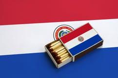 Le drapeau du Paraguay est montré dans une boîte d'allumettes ouverte, qui est remplie de matchs et se trouve sur un grand drapea photos stock