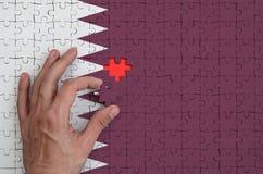 Le drapeau du Qatar est dépeint sur un puzzle, que la main du ` s d'homme accomplit pour plier photo stock
